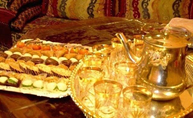 يقدم الشاي للضيوف في العيد بصينية خاصة بهذه المناسبة ذهبية اللون